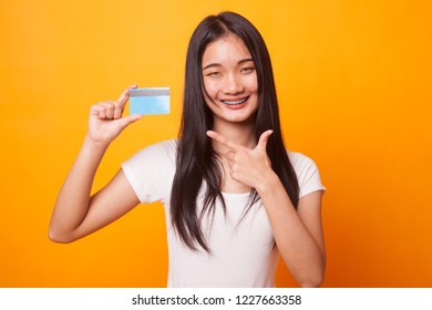 Young Asian woman point to a blank card on bright yellow background
