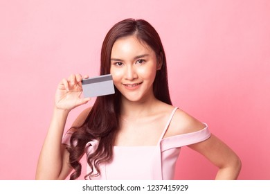 Young Asian woman point to a blank card on pink background