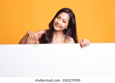 Young Asian woman point to a  blank sign on yellow background