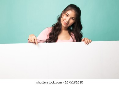 Young Asian woman point to a  blank sign on cyan background