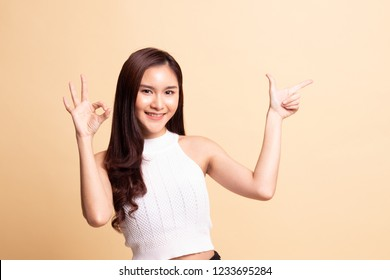 Young Asian woman point and show OK   on beige background