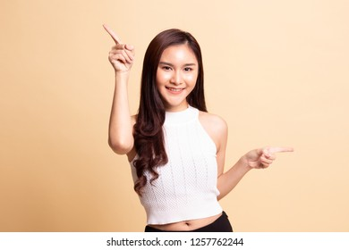 Young Asian woman point with two hands   on beige background