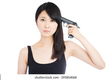 young Asian woman pointing a gun on herself