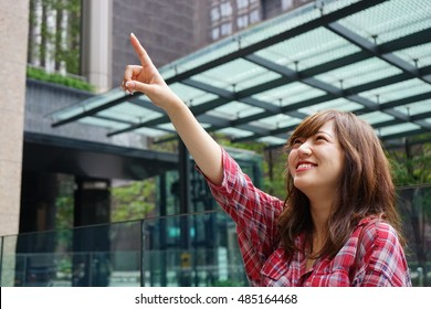 Young Asian woman pointing over there while traveling abroad