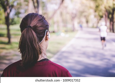 a young Asian woman with pony tail hair warm up walking before a daily exercise activity, running or jogging, by stretching her body and legs at the park in the middle of the city in a summer morning