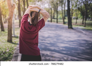 a young Asian woman with pony tail hair prepare her body before a daily exercise activity, running or jogging, by crossed stretching her arms at the park in the middle of the city in a summer morning