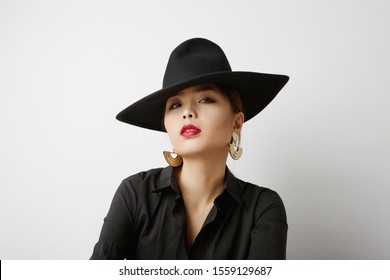 Young asian woman posing on the white background and wearing fashion clothes. Isolated.