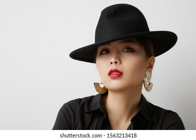 Young asian woman posing on the white background and wearing fashion black hat. Isolated.