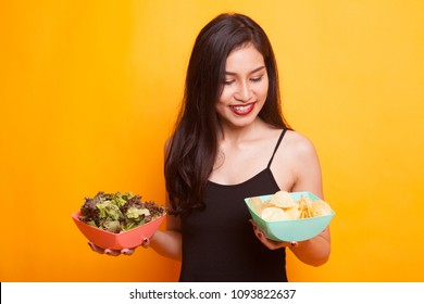 Young Asian woman with potato chips say no to salad on yellow background