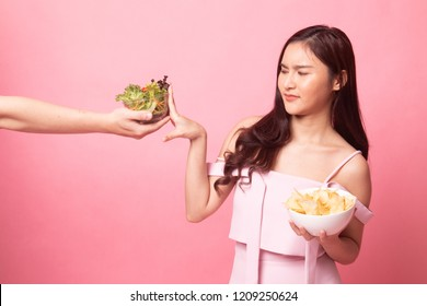 Young Asian woman with potato chips say no to salad on pink background