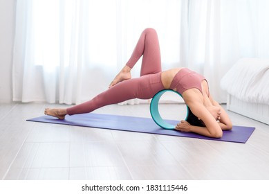 Young Asian woman practice wheel yoga to reduce strecth working from home in a bed room.