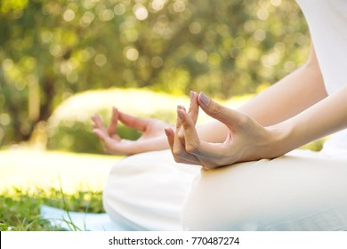 Young Asian woman practicing meditation in park. Closeup hands with copy space. Good activity for health and mind. Warm color tone. Park view with bokeh and blur background.