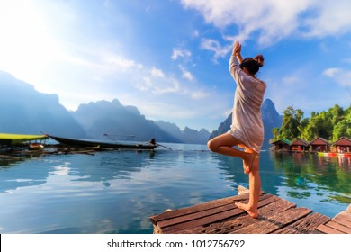 Young asian woman practicing yoga with lake mountain and clear blue sky in Thailand