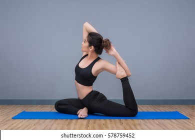 Young asian woman practicing yoga pose at yoga healthy sport gym, yoga and meditation have good benefits for health. Photo concept for Yoga Sport and Healthy lifestyle.