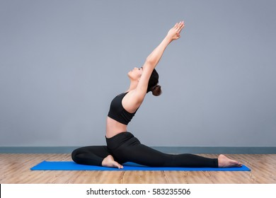 Young asian woman practicing yoga pose at yoga healthy sport gym, yoga and meditation have good benefits for health. Photo concept for Yoga Sport and Healthy lifestyle