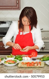 Young Asian Woman Preparing Green Healthy Food in Kitchen