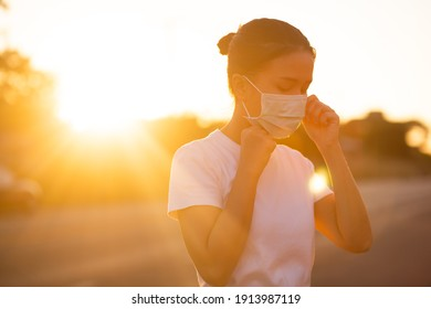 Young Asian woman putting on face mask with beautiful sunset on background. Coronavirus or covid-19 protection concept.