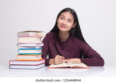 Young Asian woman read a book with books on table on white background