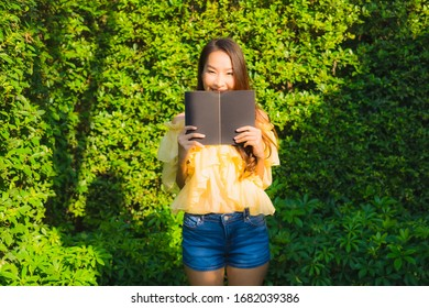 Young asian woman read book around outdoor garden nature view