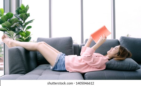Young asian woman reading book on holiday. A closeup of young happy girl lying opened book on the couch at home. Casual lifestyle at home.
