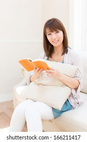 young asian woman reading book on the sofa