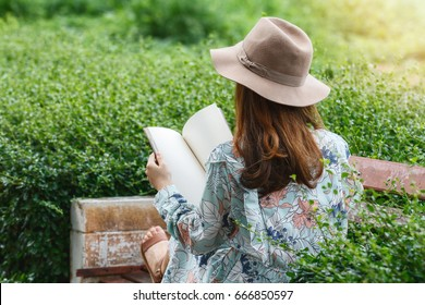 Young asian woman reading a book on the bench in park