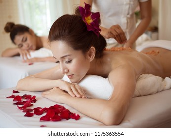 Young Asian woman receiving salt massage in spa salon