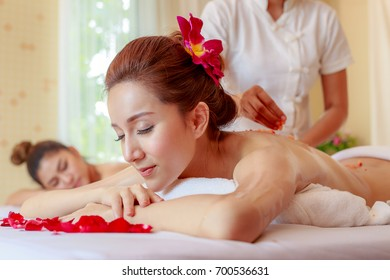 Young Asian woman receiving salt massage in spa salon, Hand putting salt scrub on female back, Spa concept