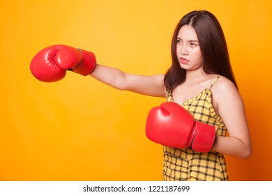 Young Asian woman with red boxing gloves on yellow background