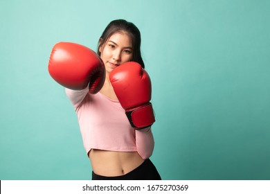 Young Asian woman with red boxing gloves on cyan background