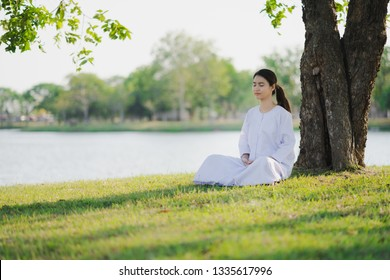 Young asian woman relaxes wearing white dress meditation at green grass fields, Thai woman Buddhism meditation in Buddhist holy day
