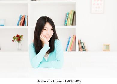 young asian woman relaxing behind book shelf