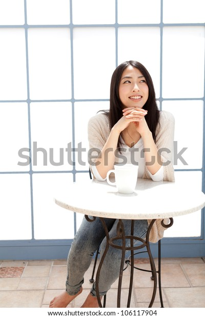 a young asian woman relaxing in cafe