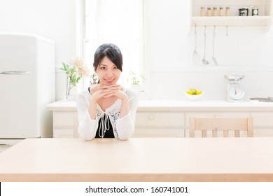 young asian woman relaxing in kitchen