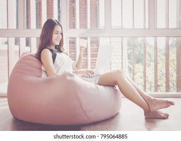 Young asian woman relaxing on a sofa at home and drinking coffee of the living room.relaxing,happy concept.