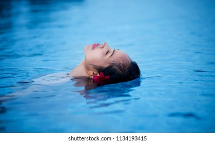 Young asian woman relaxing in swimming pool at spa resort.relaxing concept.Hot summer day and bright sunny light
