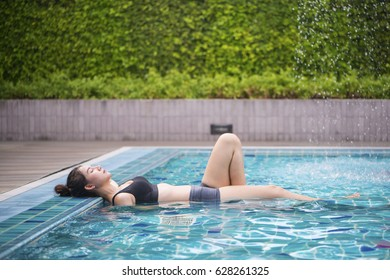 Young asian woman relaxing in the water. Summer.