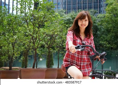Young Asian woman riding on a bike in the city