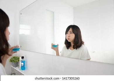 Young asian woman rinsing and gargling mouth with mouthwash after brushing her teeth in bathroom. Oral hygiene routine for freshness breath, prevent plaque and gum disease. Dental health care concept.