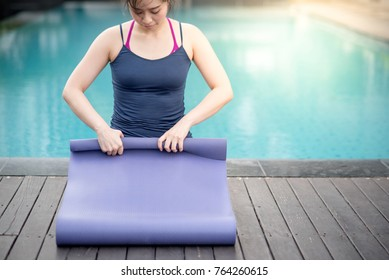 Young Asian woman rolling purple yoga mat at swimming pool, outdoor exercise and healthy lifestyle concepts