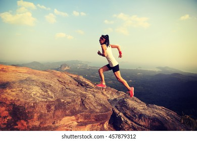 young asian woman runner running on mountain peak