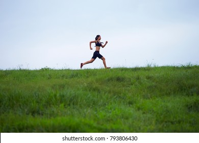 young asian woman running in the grass field
