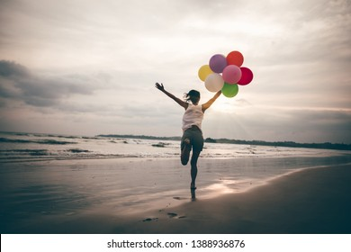 young asian woman running and jumping on seaside with colored balloons