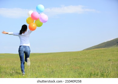 young asian woman running and jumping on green grassland with colored balloons
