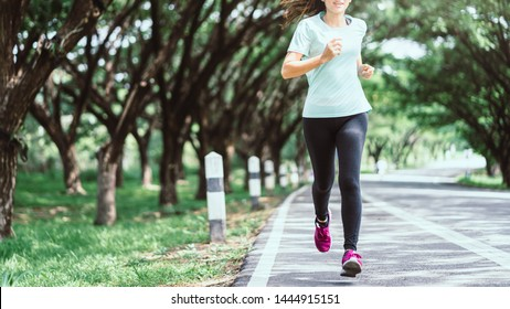 Young asian woman running on road in the natural background.