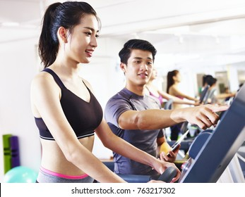 young asian woman running on treadmill coached by young male trainer.