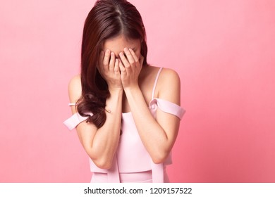 Young Asian woman sad and cry on pink background