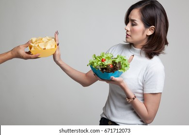 Young Asian woman with salad say no to potato chips on gray background