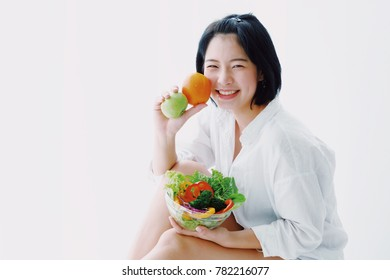 Young Asian woman with salad vegetables on white background