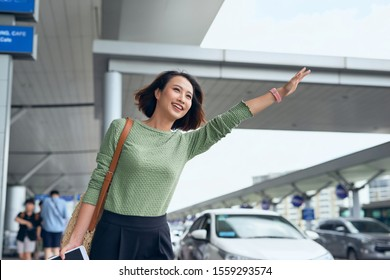 A young Asian woman see her car that her booked via a ride hailing app and are waving it down